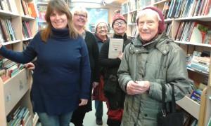 Bibliotekarierna Camilla Enblom och Catharina Brolin-Nilsson på bokbussen med glada låntagare vid hållplatsen i  Vamlingbo.
